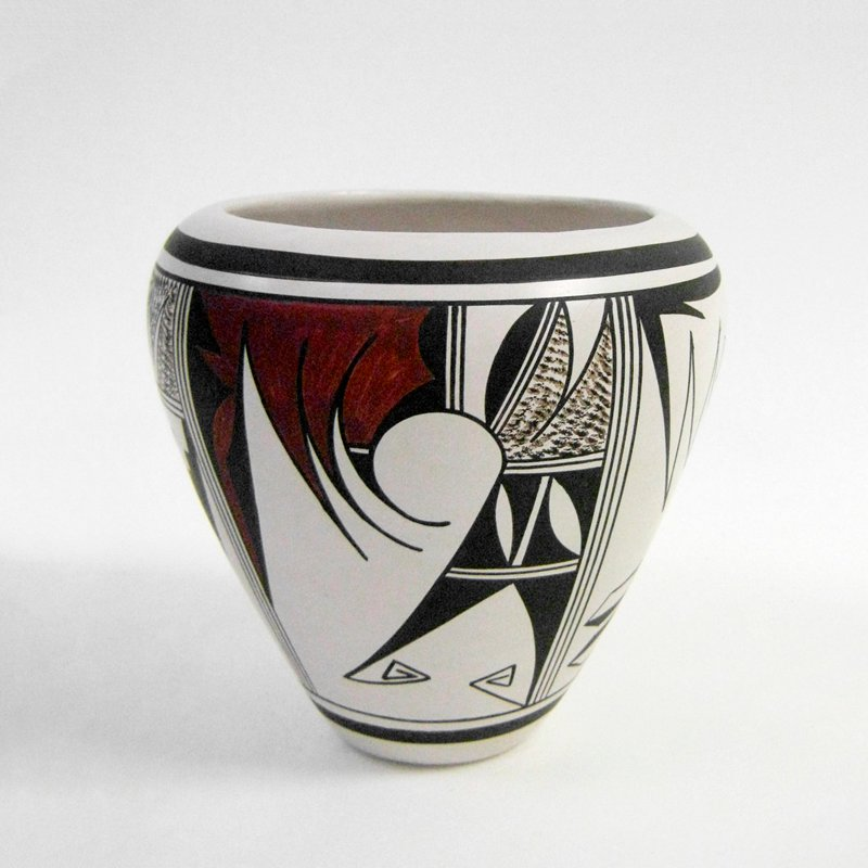 white ground; 2 pairs of alternating geometric designs in dark and chocolate brown; vessel has small foot, flaring outward to short shoulder and wide mouth