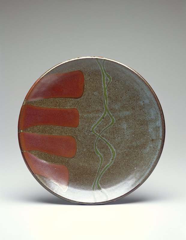 small stoneware plate with foot; interior of bowl decorated by four large brown fingers from one edge and two green intertwining lines across diameter over a dark green overall glaze