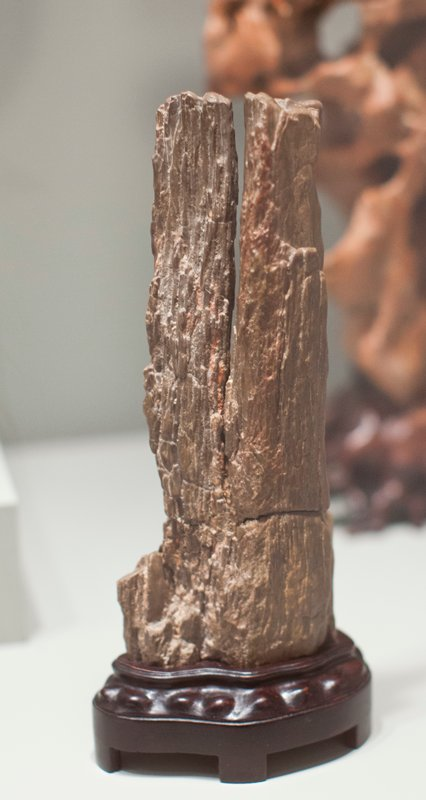 vertical rock with linear striations of red and brown; wood stand attached