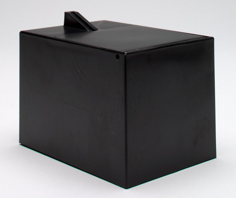 rectangular black box; wedge-shaped coin slot; battery operated; trap door on top; unknown mechanical action
