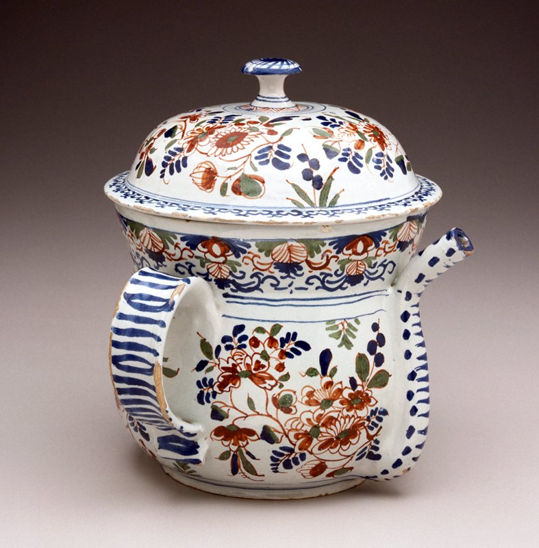 Polychromed floral pattern of blue, green and red; wide handles on either side with spout front center