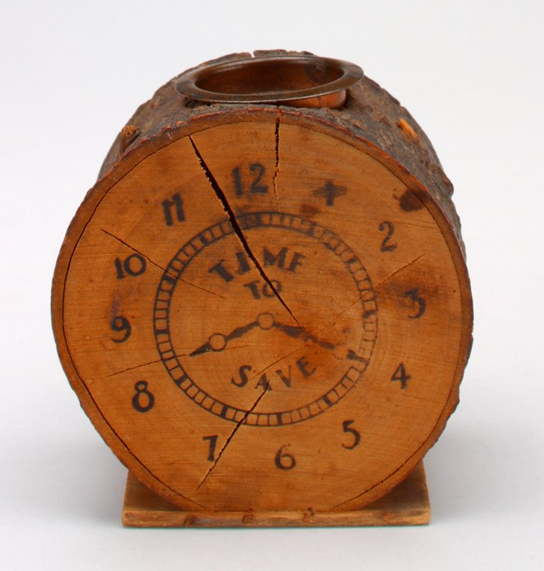 varinshed log with clock face, illegible lettering on small wooden base; copper slotted removable top; dark brown printing on clock face;