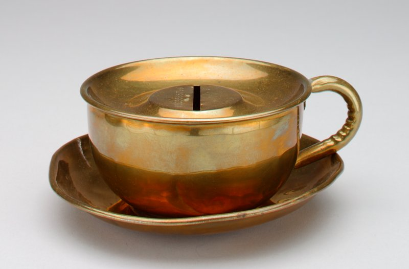 brass colored cup and saucer bank; cup has handle and is covered with a slot in the center