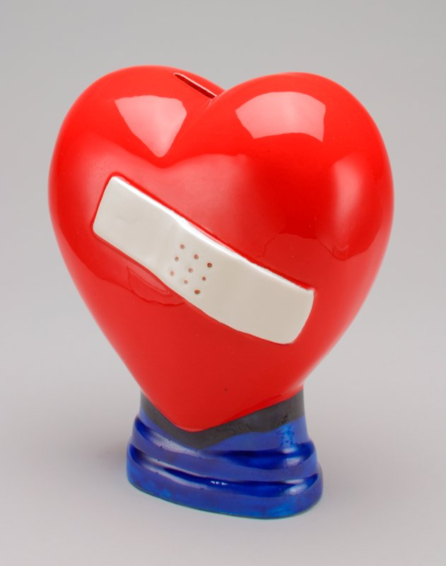 ceramic bank in the form of a red heart with a white bandaid across it, sitting on a blue base; yellow plastic stopper on bottom
