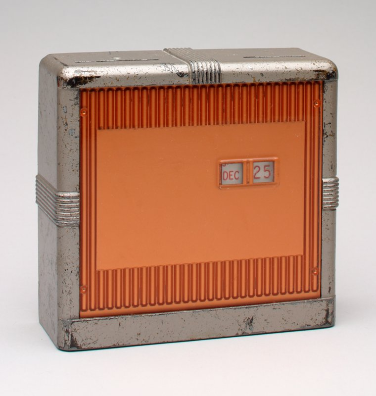 square silver metal calender bank with copper colored plastic front; 2 windows in front for month and day