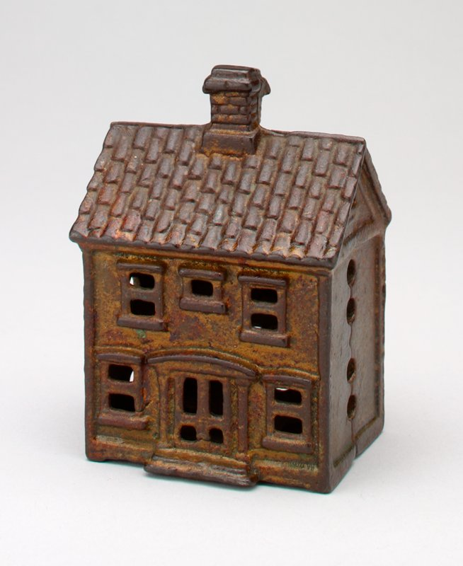 small 2 story building with chimney, door and 2 windows with pediments front & back; 3 windows front & 2 back on second story; coin slot in back
