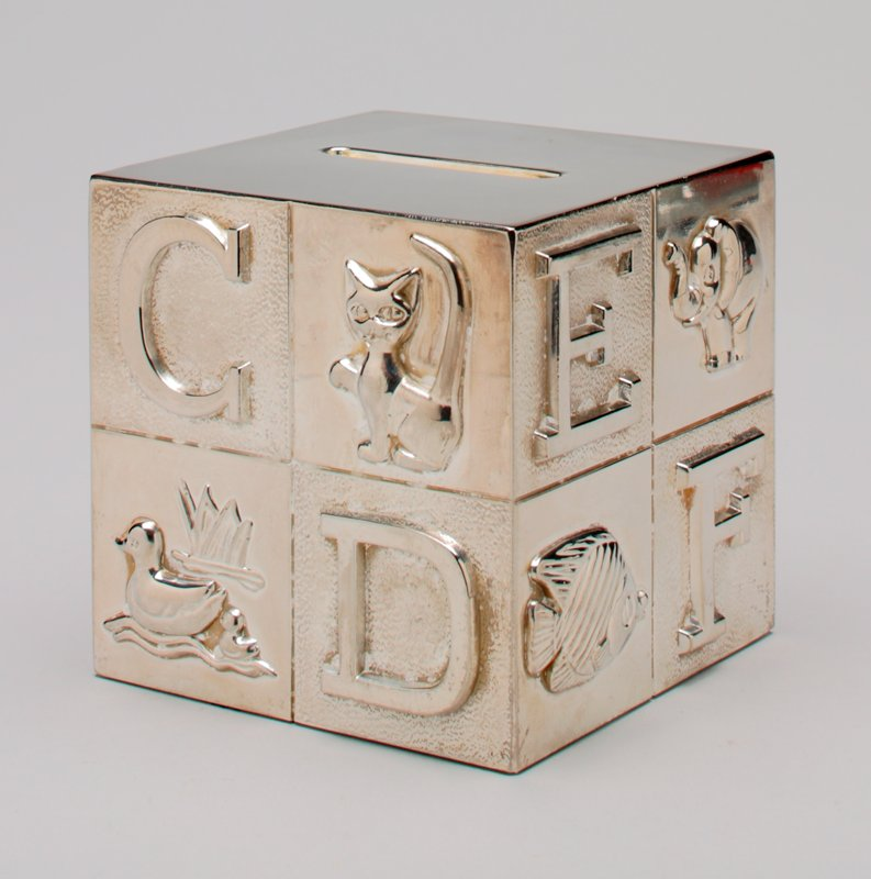 silver plated toy building block; letters A through H, animals, and fruit on the sides; blue felt glued to the bottom; coin slot on the top