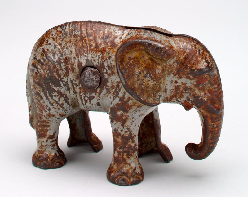 standing grey elepahant, red eyes and mouth; trunk down; coin slot in back; large bolt with nut through body