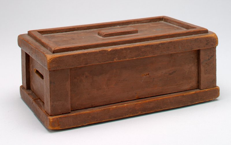 plain dark wood box with panels on top, sides and ends; coin slot in end panel