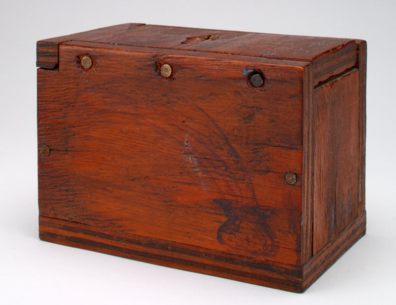 dark wood box with ink drawing on top sides and front- coin slot in front; 'Nov. 1904' on back