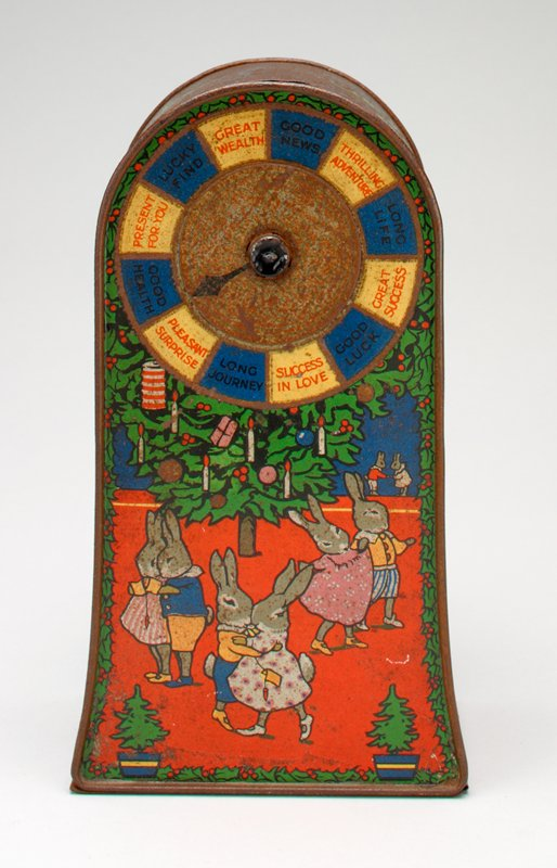 brick shape with rounded top; scenes of rabbits having holiday celebration on front and sides; spinner with wishes for good fortune on front; coin slot in top