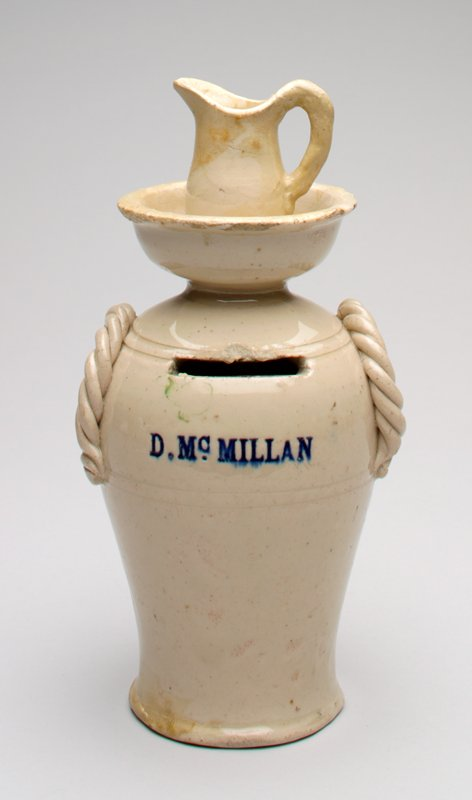 vessel with twisted handles on each side; a wash basin with pitcher sits on top; a coin slot on front with the name D. McMillan below it; color is natural with a shiny glaze; rings incised around top and center