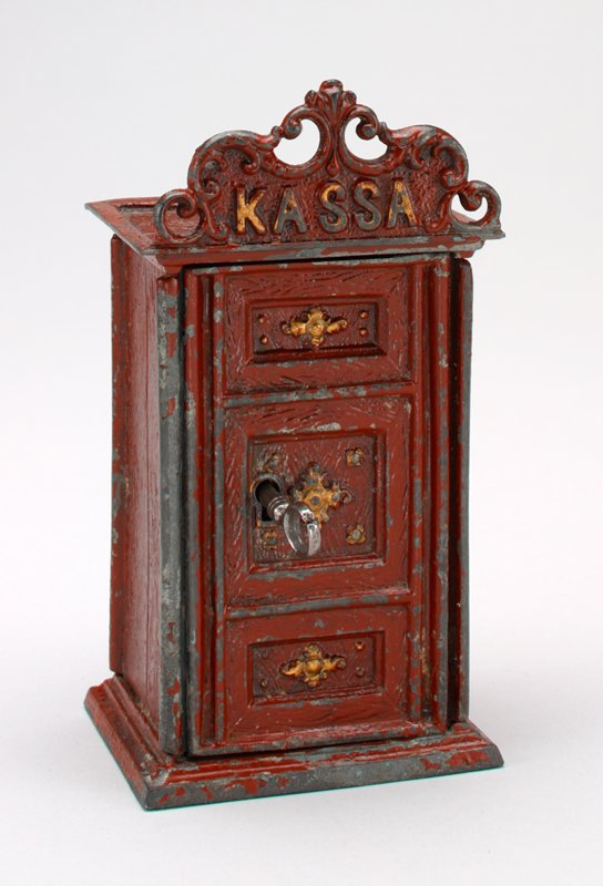 "metal rectangular red cabinet with gold trim; keyhole in front door; wood grained; fancy top piece labeled ""Kassa""; coin slot on top"