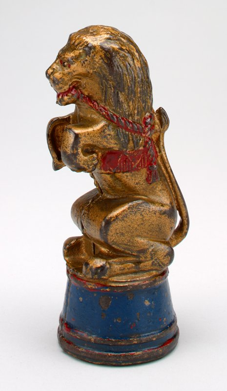 gold metal performing lion standing on his hind legs wearing red harness; he is on a red and blue drum-shaped pedestal; tail raised up his back; red rope in his mouth