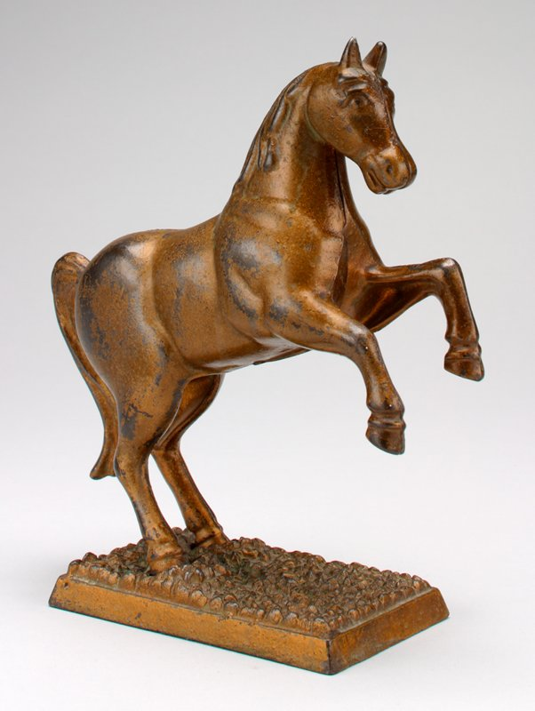 bronze color horse with two front legs off ground; coin slot back of neck; standing on an attached rectangular base