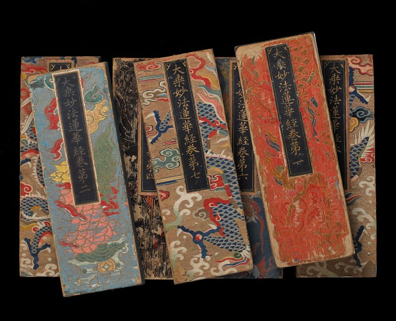 seven volumes, each covered in dragon-patterned fabrics; blue pages with text in gold with some red characters at beginnings and ends of volumes; volume with orange front cover and blue back cover has six-leaf painting on front pages in gold, blue and green; volume with gold front cover and pink back cover has two-leaf painting on back pages; volumes contained in a silk-lined wood box with removable cover