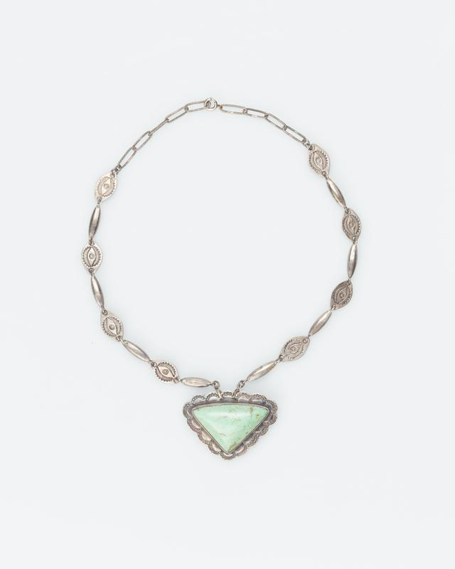 single strand of faceted long silver beads and stamped plaques; triangular turquoise set in silver with stamped design of scallops; pendant is also a pin; old chip in stone