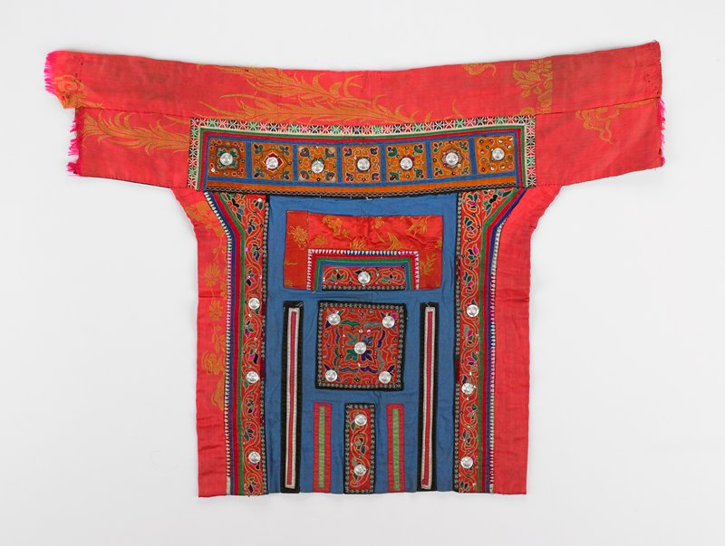 T-shaped red and gold damask borders on three sides; top section has embroidered inset with seven squares of chain stitch flowers, sequins and metal medallions on orange with blue borders; larger section includes some embroidery with 14 medallions on squares and rectangles; back lined in blue and black