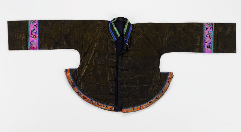 bronze indigo; opening has 5 frog fasteners; stand-up collar with bands of silk damask in blue, green and black; flared bottom hem has orange embroidered band; sleeves have embroidered pink bands; lined in dark blue gauze