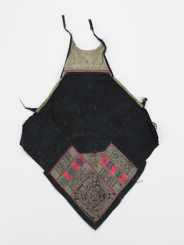 """black diamond shape apron; added batik bib with 2 ties; lower third has sections of geometric embroidery and applied tape in red, green, purple, and white divided by 3/8"""" red tape; 1"""" loops at side"""