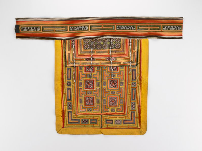 broad band across top with wide rectangular panel and 4 long seed tassels which lay on top of squares surrounded by geometric applique and geometric embroideries in yellow, red, green and white; overlay rectangle and band have narrow applique and embroidery in similar colors; one long tie on PL of band