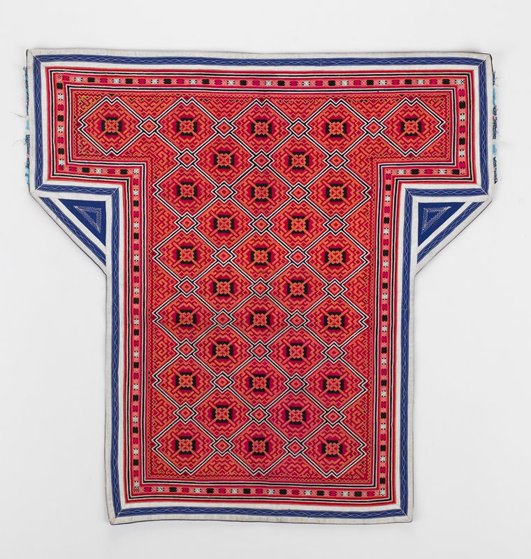 completely embroidered in interlocking diagonal squares in orange, red and black with smaller diagonal squares connecting; white and black outlines; outer border of blue and white applique strips; blue lining