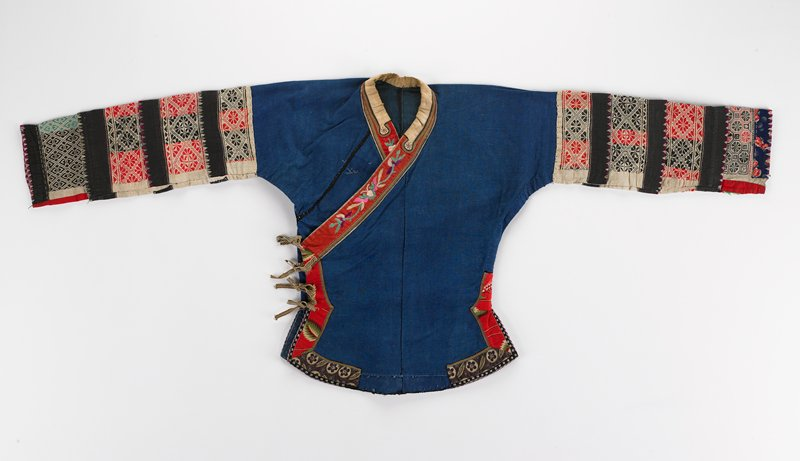 """likely woman's blue jacket with nipped waist and curved bottom; side opening with four sets of woven ties on PR; stand-up neck band has embroidered red facing; front and back bottom have partial and complete bands of multicolored embroidery and printed material; sleeves have four bands of cross stitch red and black on tan with brown overlaps; back has 8-1/2"""" x 13-3/4"""" rectangular red applique with tiny black and white appliques in geometric field"""