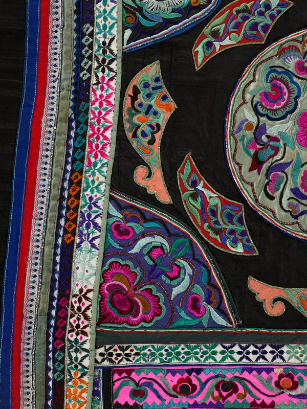 black silk square with green silk circle medallion, surrounded by abstract shapes and triangle corners; all embroidery in floral satin stitch, metallic and multicolor; bordered in embrodery and appliqued strips; bottom center strip is brilliant pink, green and purple; bottom flap and wide strap holders are piped in brown
