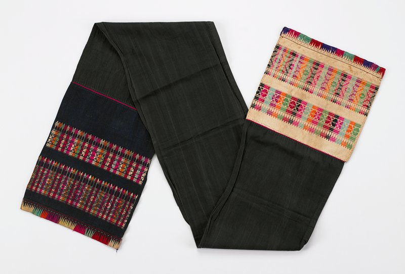 "black; 9-3/4"" ends of belt have handstitched 2-3/4"" and 3-1/4"" bands of geometric embroidered design, one end on black, one on tan; 1"" embroidered flame design hems; red, green, orange, pink, purple, tan, black"