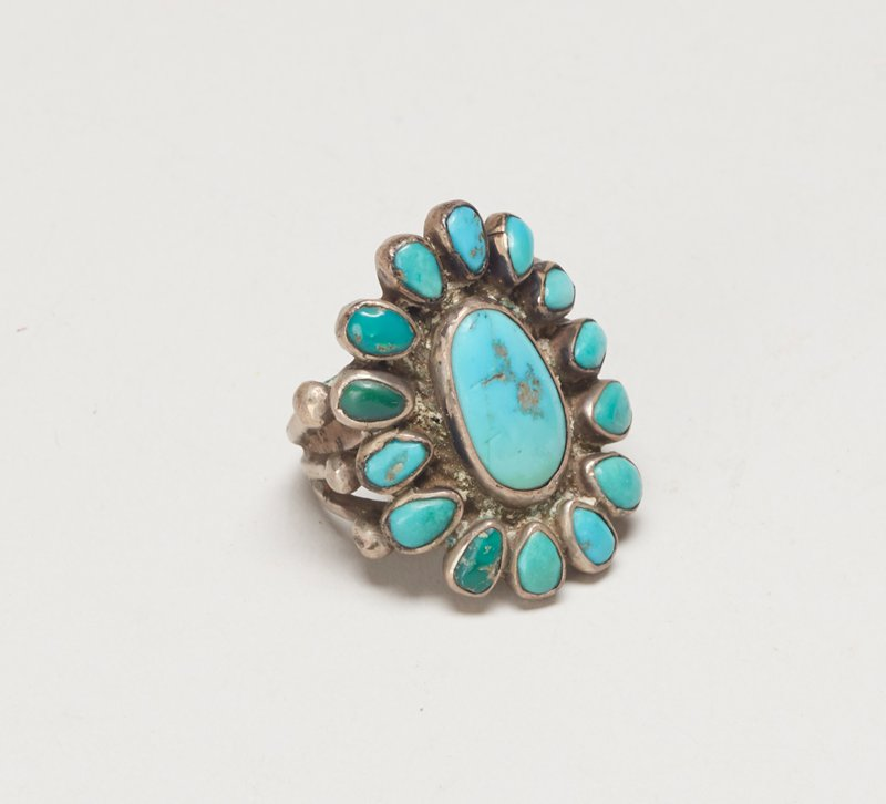 triple-branched band silver ring with central turquoise surrounded by 14 smaller turquoise; bands end in silver drops