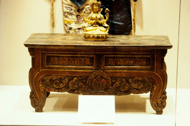 small wood table, top slants slightly toward back; front and sides carved in low relief with religious symbols and lacquered, single horizontal support brace at back; cloud design at front with two rectangular inscriptions at top