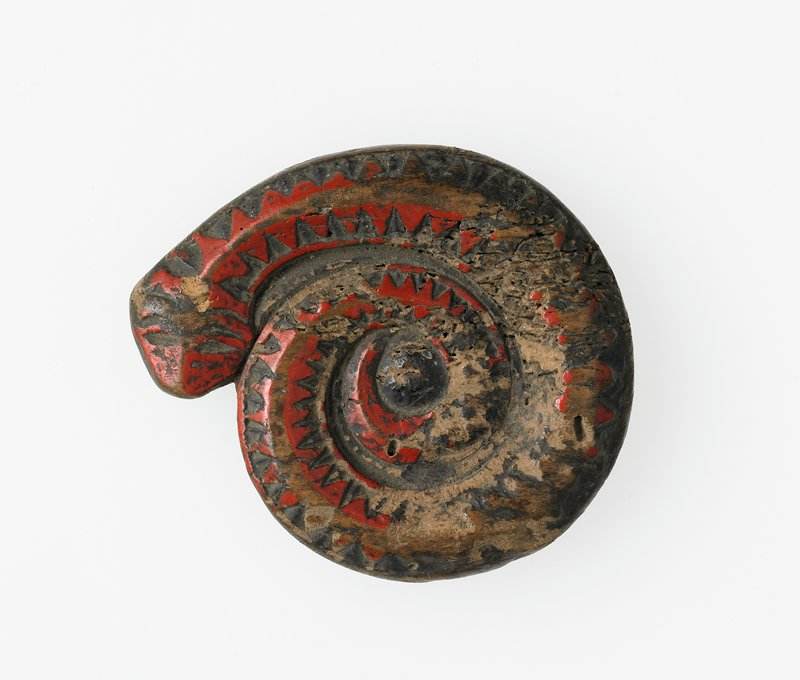 shaped like coiled snake with zigzag decorations; disk at center of coil carved with treelike symbol