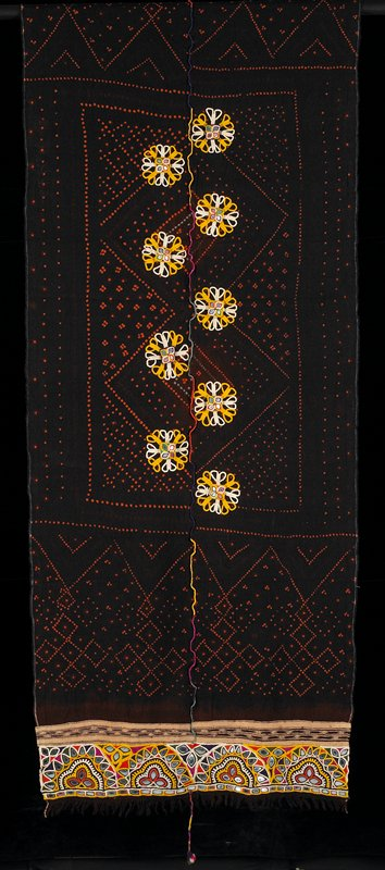 black veil with orange tie-dyed designs of diamond and dot shapes and borders; nine yellow and white embroidered medallions with raised four-mirror centers near center, multi-colored center strip; border of heavily embroidered and mirror designs at both ends; bottom end has center, dangling pompom; two selvedges; two fringed ends