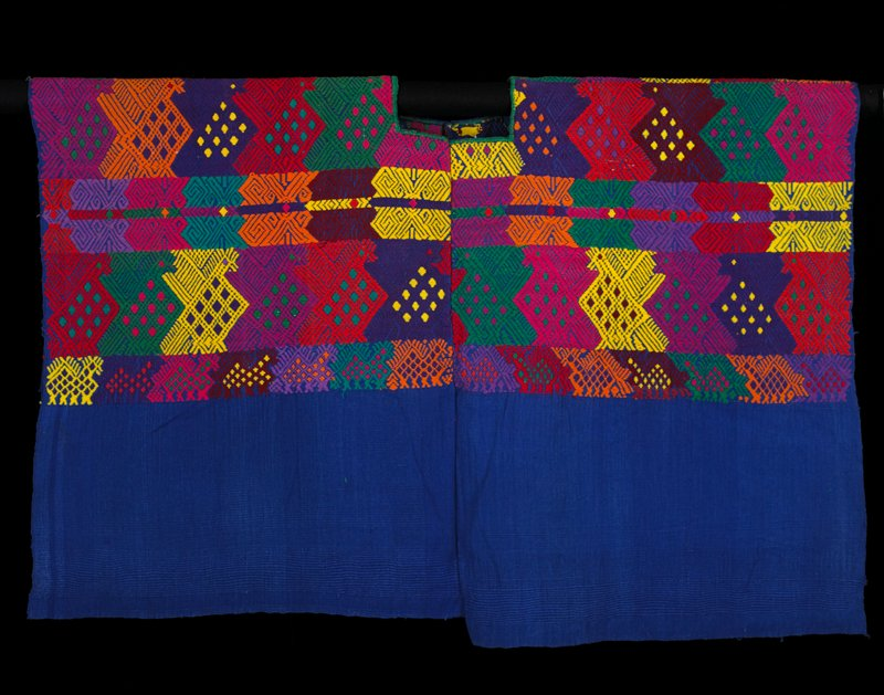 two wide blue cotton paneled huipil; woven on a back strap loom; brocaded with large multicolored zoomorphic designs (butterfly, lion, turkey); brocade is woven on the two-faced brocade technique; panels are finished in four selvedge ends; square neckline is cutout and finished with a hand embroidered seam