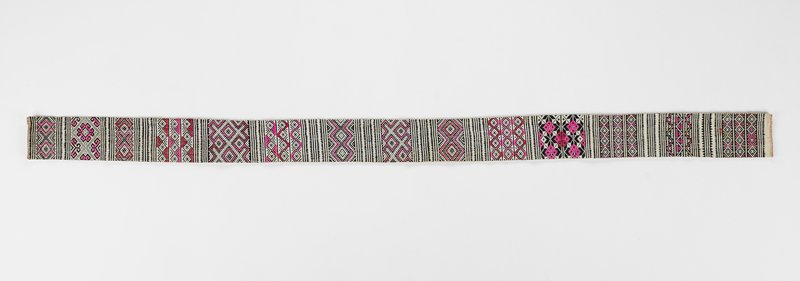 long white band with rows of black and white embroidered geometric patterns; pink and red accents; lined in white