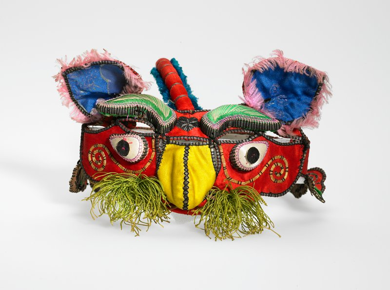 red, yellow, green; open band design; dragon face; yellow nose; green brows; black and white eyes; blue ears; green whiskers; red background; pink and blue fringe; red tail with tassel; some embroidery; yellow metal on cheeks; paper lining