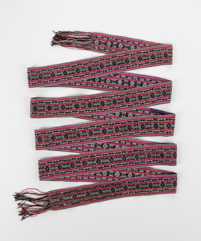woven horizontal stripes separated by geometric pattern in red, pink, black and white with knotted self fringe