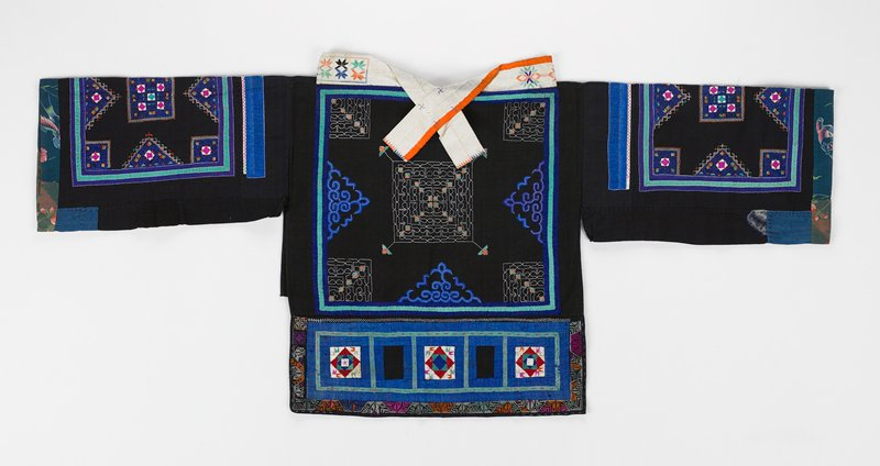 "tunic style black jacket; open at sides; stand-up collar with ties front and back in white; back is longer and embroidered with squares on four corners and center in white running stitch accented in orange and green; three sides have blue applique triangles; blue and green strips surround back; bottom 6-1/4"" panel is appliqued with five squares and cross stitch; sleeves have similar design"
