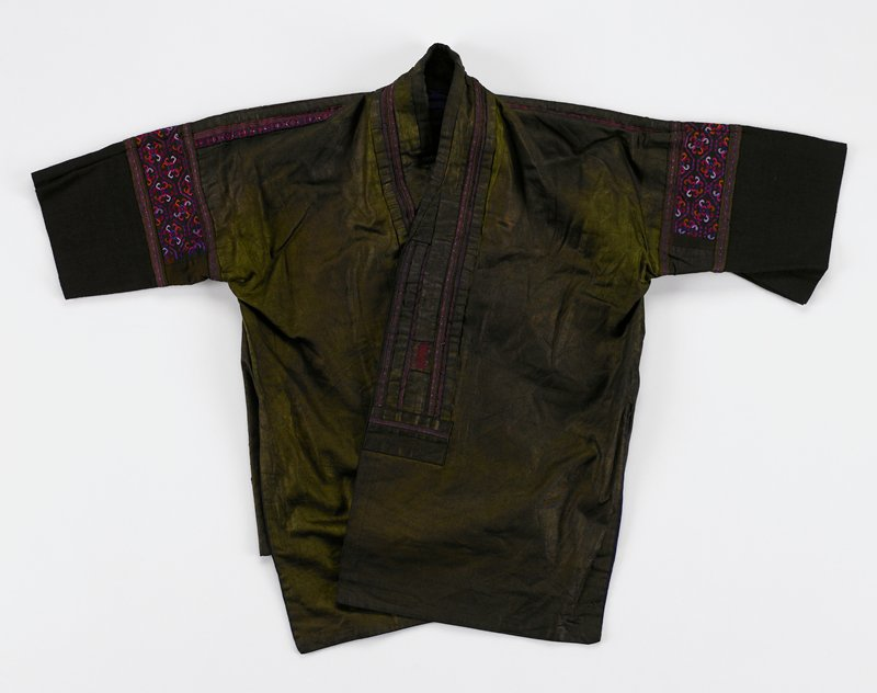 newer; front opening bronze color with purple and red tape applique on collar; bands of commercial embroidery on sleeves and shoulders in blue, red, orange; back is covered with woven fabric of diamond pattern inset with ribbons and bronze borders; purple lining and cuffs