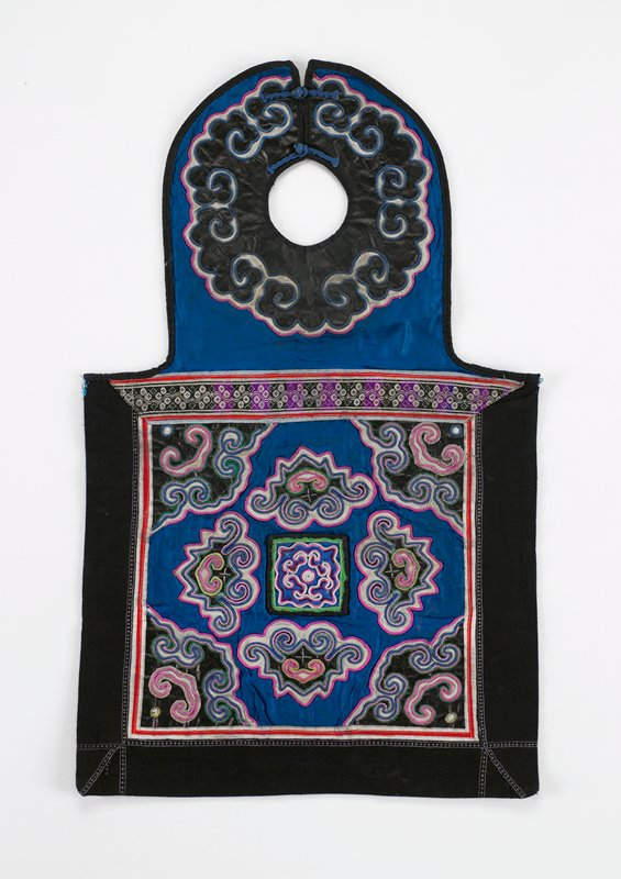 neck piece fastened by two frogs; scrolled applique on pounded indigo on blue silk edged in red; bottom blue silk square bordered in black has eight irregularly shaped appliques embroidered in pink, white and green with metallic thread; separate loose applique and embroidered square attached to center of bottom section; black pounded indigo lining