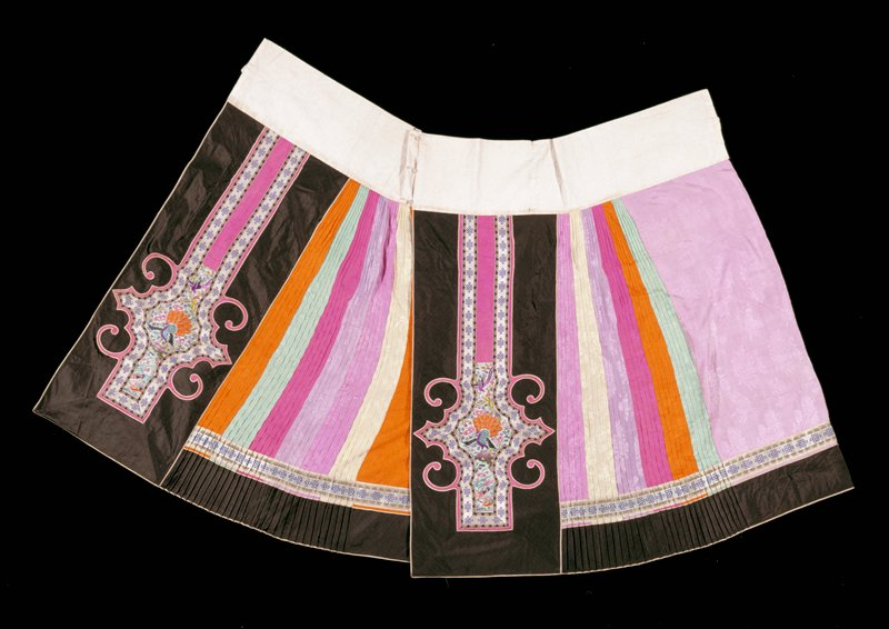 in 2 sections; black with embroidered peacock motif; pink, lavender, orange, green pleated sections