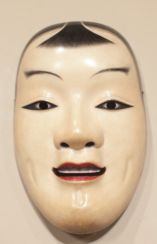 human face mask with smiling mouth with red lips and top teeth visible; wisps of hair at sides of face and small fringe of bangs; mouth, irises and nostrils cut out