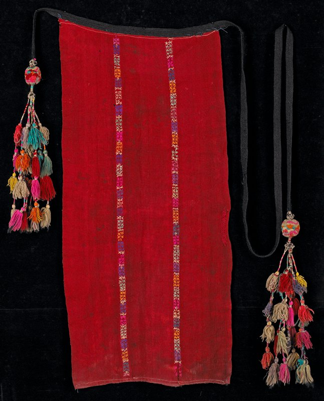 "red wool with two vertical rows of embroidered ""characters"" down front; black braid belt with multicolored tassel endings hanging from pompom"