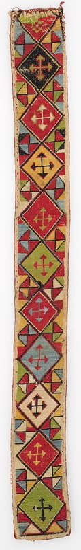 Warp-twined (LM) band fragments. Pieced ikat and printed lining. Overall cross stitch embroidery on a cotton ground. No edging or trim is present. One end has been folded under and wear is seen along the fold. There is a red printed cotton backing, under a silk/cotton ikat backing. Diamond shapes with arrows. Red, yellow, blue, green.