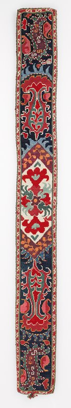 Warp-twined (LM) edge, Printed lining. Overall cross stitch in silk thread on a cotton ground. Applied woven bands form an edging on the four sides. Remnants of a tassel are seen at the center of one short side. The backing is red printed cotton fabric. Red, blue and white dominate.