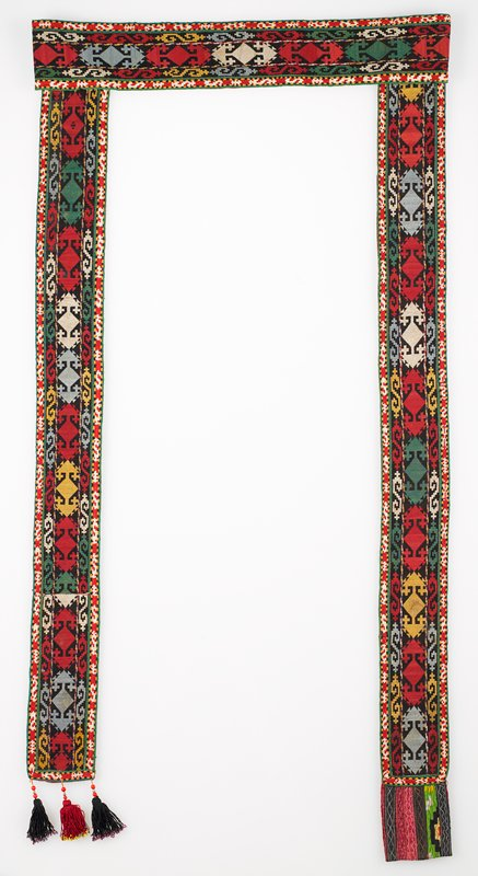 """Embroidered band, Pieced, printed lining. Overall cross stitch embroidery in silk thread on a cotton ground. There is an integral border worked in chain stitch. At one end are three silk and cotton tassels trimmed with metal and plastic beads, tipped with glass beads. At the other end is a machine-stitched pieced tab incorporating cotton, silk, and rayon fabrics. Two red printed cotton fabrics form the backing. """"a"""" is lined with red print. Tassels black, red black. """"b"""" tassels red, green, red."""