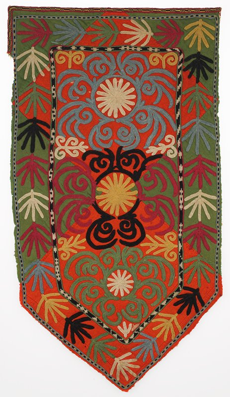 Warp-twined (LM) band. Pieced red and green wool flannel ground with polychrome silk embroidery. There is a block printed cotton substrate beneath the wool. The top edge and the upper four inches of the PR edge retain a narrow embroidered silk finishing band. The remaining edges are raw. There is no backing. Center shield-shaped design surrounded border. Embroidered through backing. Chain stitch.