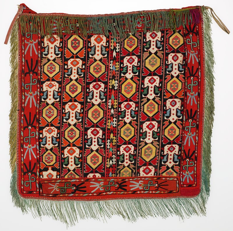 Fringes with warp-twined (LM) heading, wide embroidered bands . Overall cross stitch embroidery in silk, synthetic, and cotton threads on a cotton ground with center vertical join. The borders are attached red wool bands with chain stitch dominating, backed with cotton fabric. The panel is trimmed with cotton fringe. There are two intact hanging loops. No backing is present; the construction technique is clearly visible on the reverse.