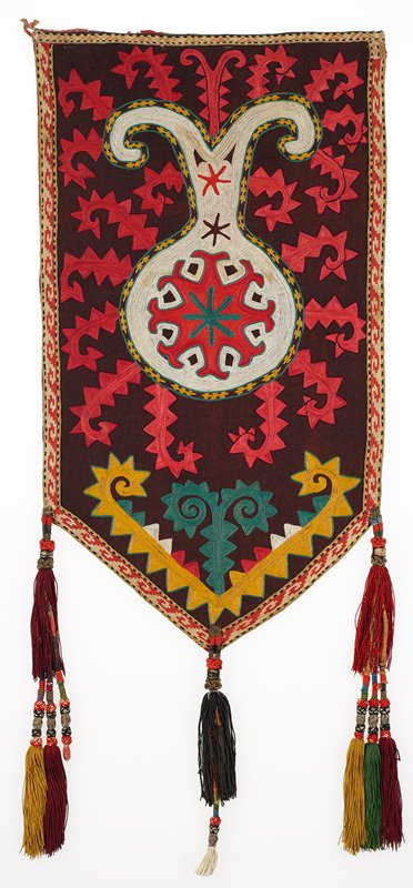 Embroidered bands. Pieced dark red wool ground with polychrome silk embroidery. Chain stitch bands in two designs outline the edges; one pattern on top edge and upper inch of PR side, and a different pattern on the other edges. Three tassels are composed of cotton, silk, and metallic threads over a cotton core. The embroidery is presently hand stitched to a fabric covered mount; the verso is not visible. Mounted and stitched to white scrim and sheer screen and a white linen covered strainer. Red.