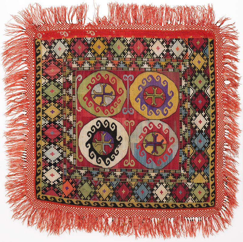 """Braided-net fringe, cloth band, Pieced, printed lining. Overall silk cross-stitch embroidery on a red cotton ground. There is a cotton binding on the edges, and a crocheted cotton fringe with tassels. The backing is red printed cotton fabric. Red, white, black, yellow, green. Four center medallions with center crosses surrounded with hook design. 4 1/2"""" border of geometric cross-stitch on all four sides. 3 1/2 fringe (braided and wrapped) all four sides. Patched, red print lining. one face edge: strip of red print."""